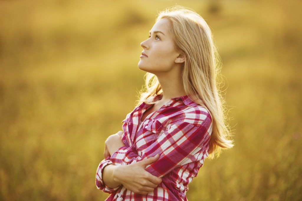 girl in sunny field looking up
