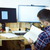 Young man in home office reading book