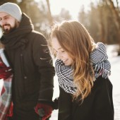 Young hipster couple walking in winter forest holding hands
