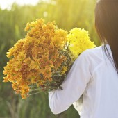 abstract woman with bouquet flowers vibrant in hands on grass fi