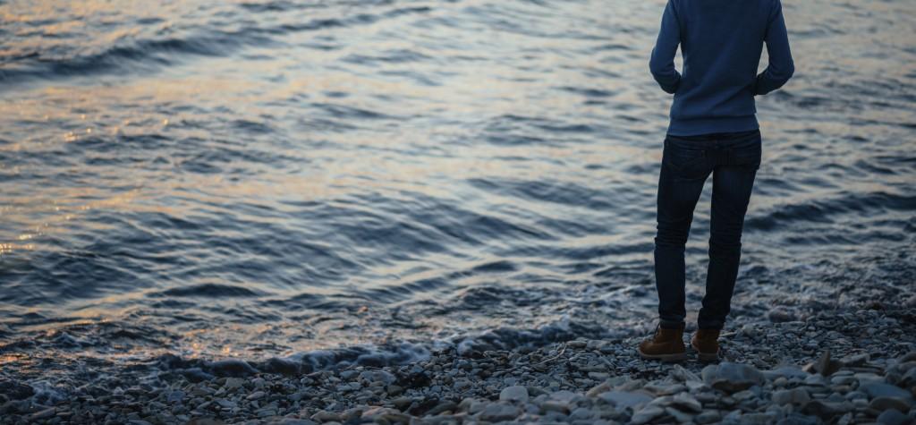 Woman walking on coast in the evening