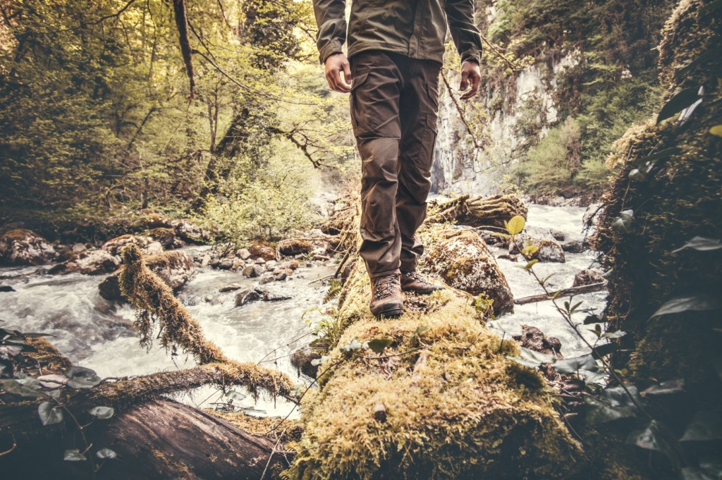 Feet Man hiking outdoor over river in forest