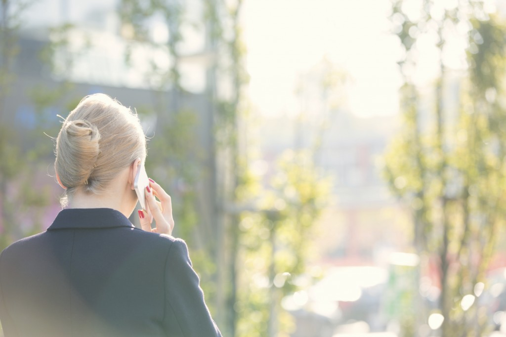 Rear view of businesswoman using cell phone on sunny day