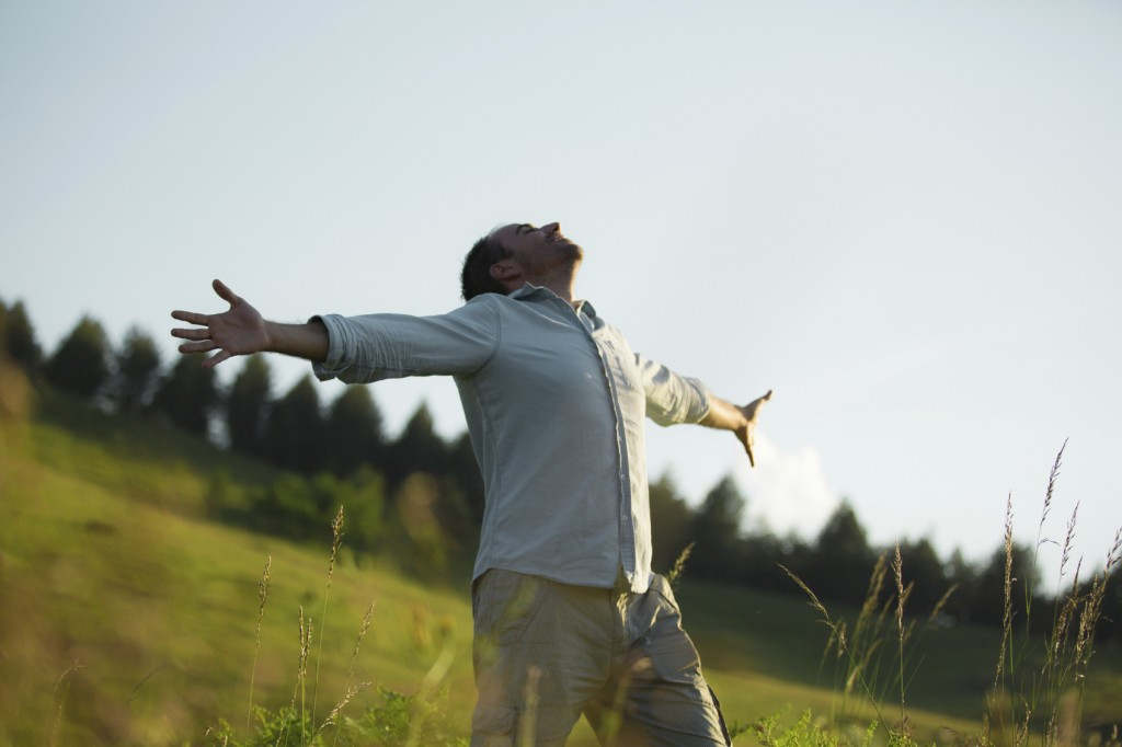 Man in fields with arms raised in worship