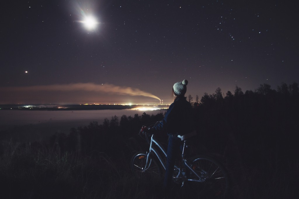 Woman with a bicycle looking at the night landscape