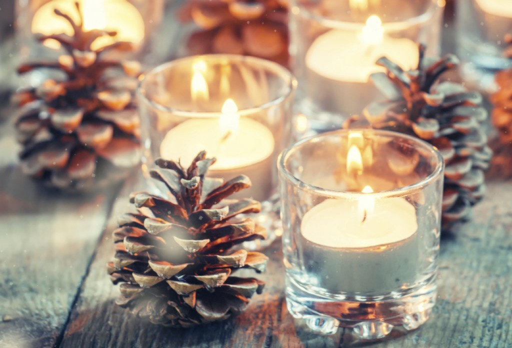 Christmas Christmas card with glowing small candle and fir cones on old wooden background,