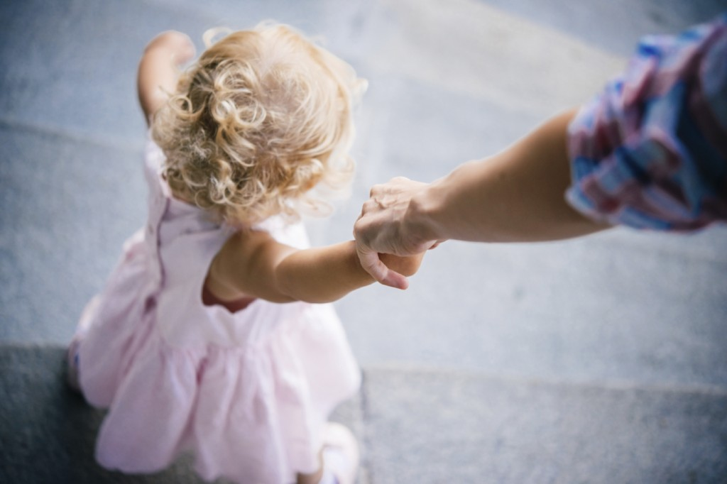 Mother holds her daughter's hand during a walk outdoors