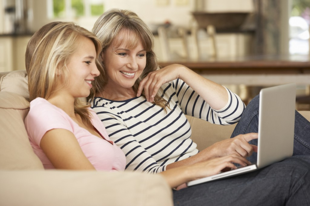 Mother With Teenage Daughter Sitting On Sofa At Home Using Laptop