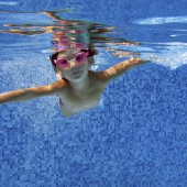Happy child swims underwater in swimming pool
