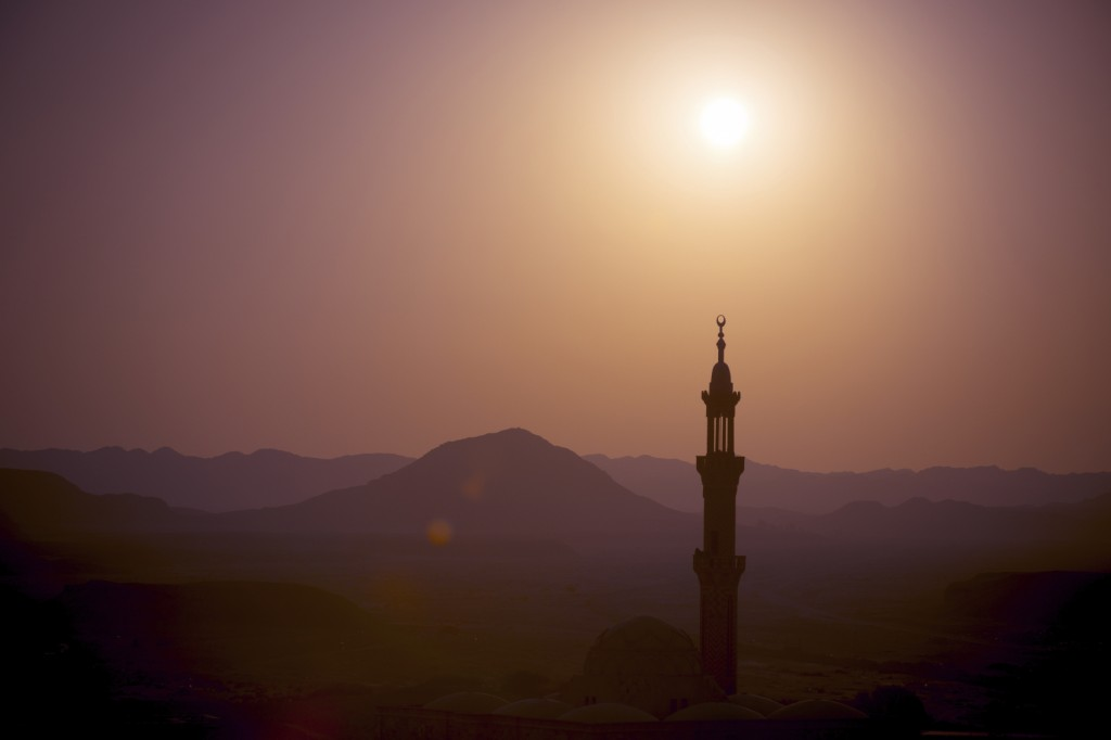 Sunset over desert with muslim mosque