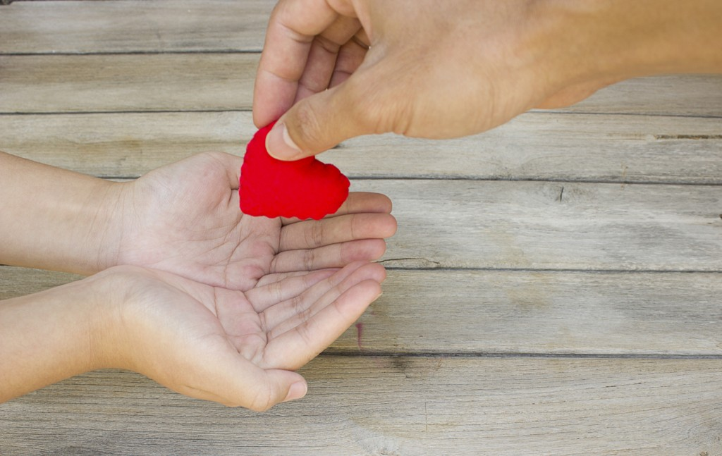 Concept of giving, giving a felt heart to another.