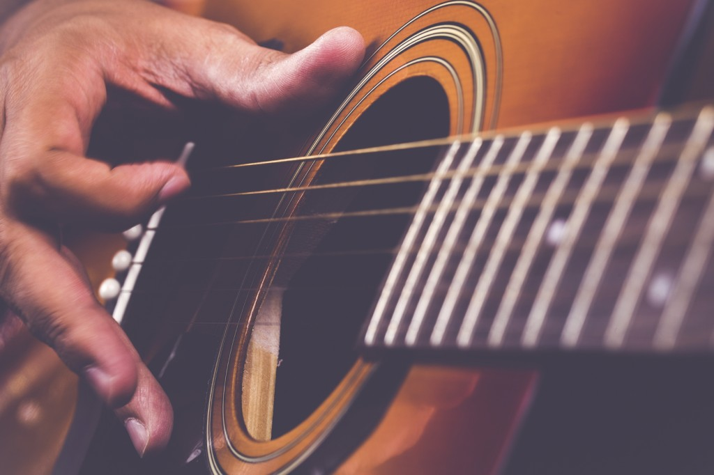 Guitarist Tending to his Instrument