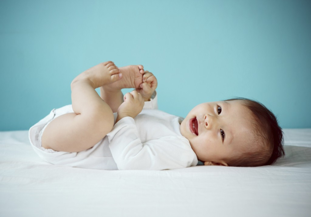 Portrait of a cute baby lying down on a bed,