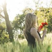 Blonde woman harvesting poppy
