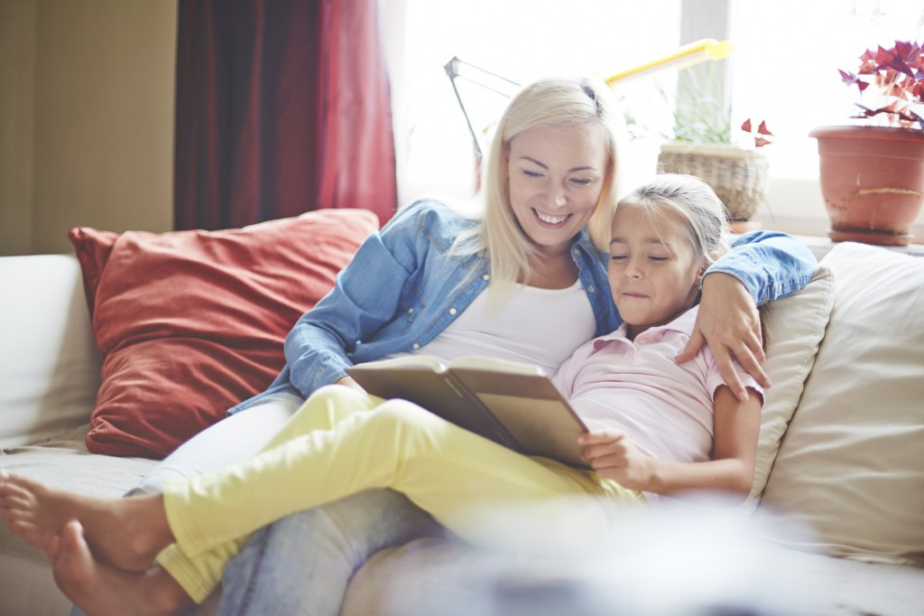 Mom and little girl reading book at home