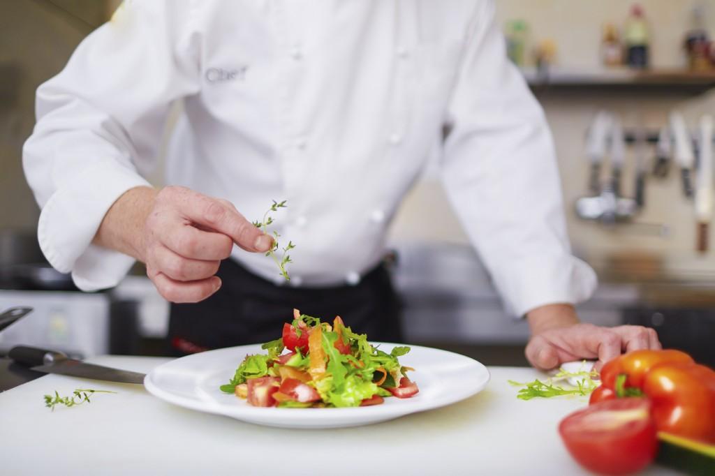 Male chef garnishing dish at the kitchen