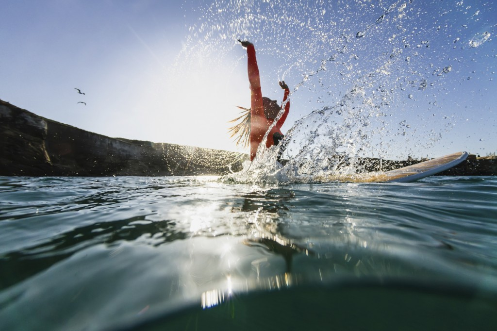 woman sitting on the surfboard and doing splashes
