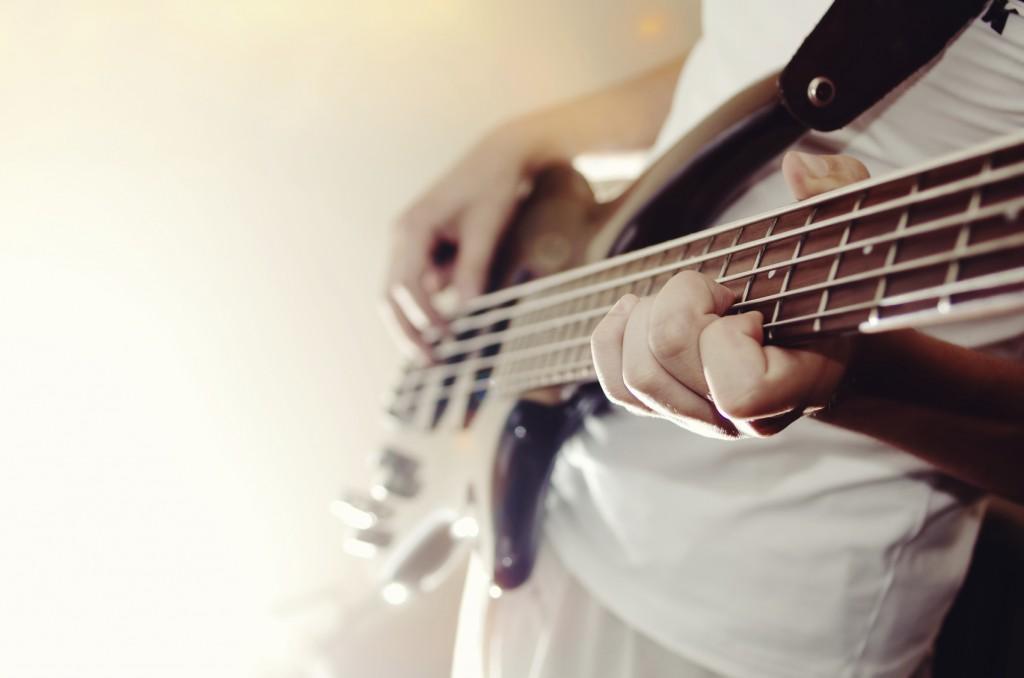 man practicing bass guitar close-up