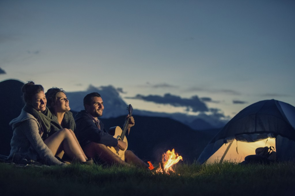 Three friends camping with guitar singing on mountain at night