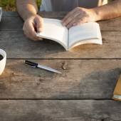 Man Reading a Book on Woodern Table