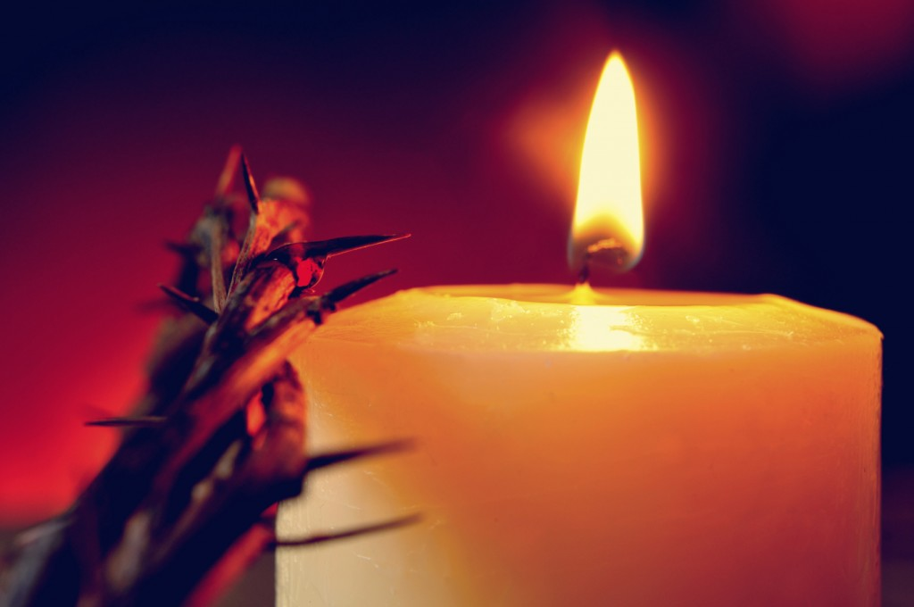 the crown of thorns of Jesus Christ and a lit candle