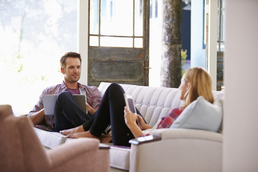 Couple At Home On Sofa In Lounge