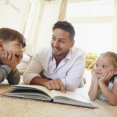 Happy young family lying on the floor reading a book