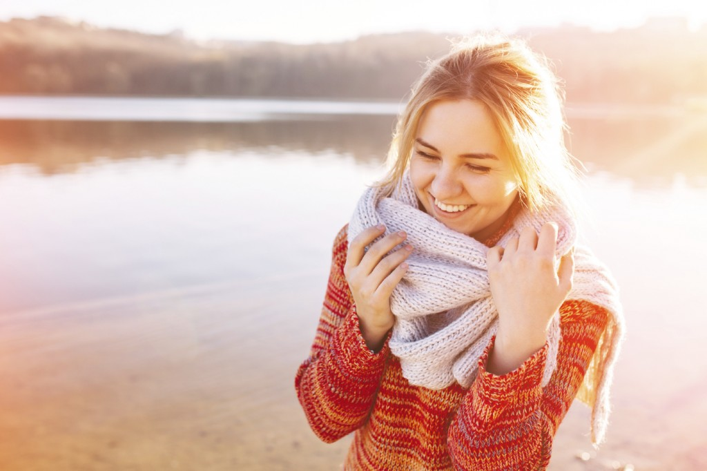 Happy young girl wearing warm clothes standing and smiling by a