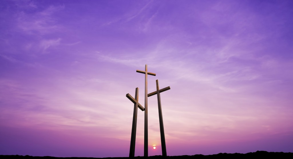 Three crosses on a hill over bright sky