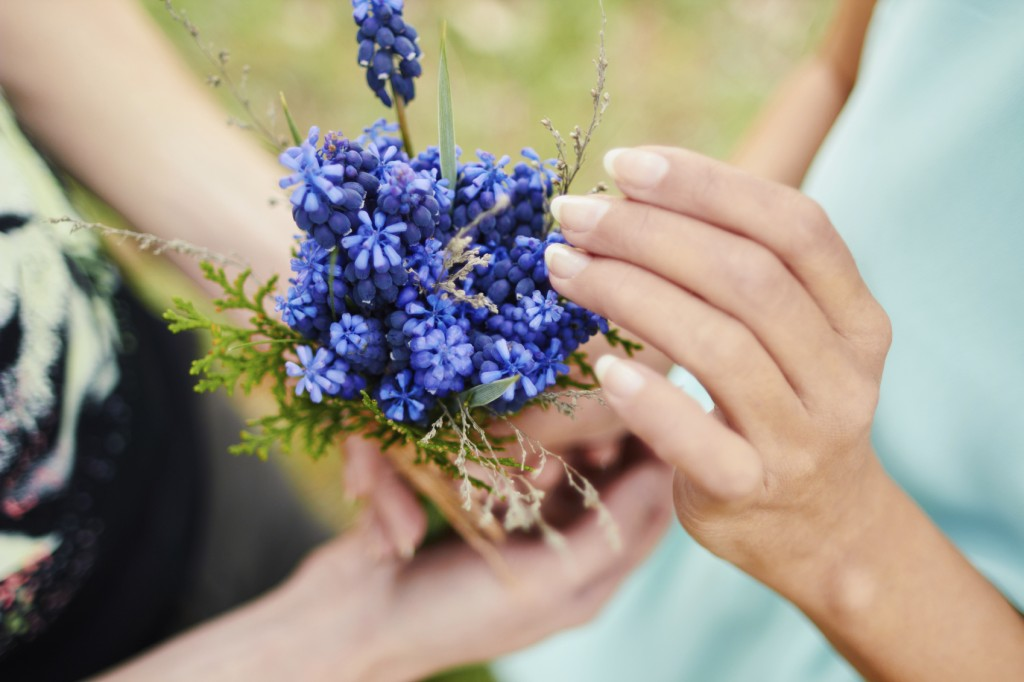 Lovers hands holding a bouquet of flowers