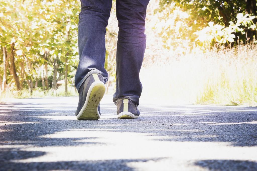 Man wearing jeans walking on the unknown street.