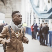 Young black man in London walking on Tower Bridge