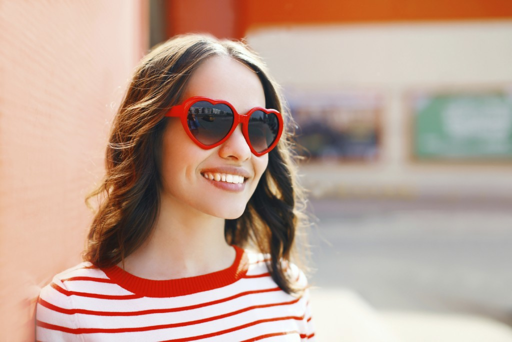 Portrait of pretty smiling woman in red sunglasses outdoors