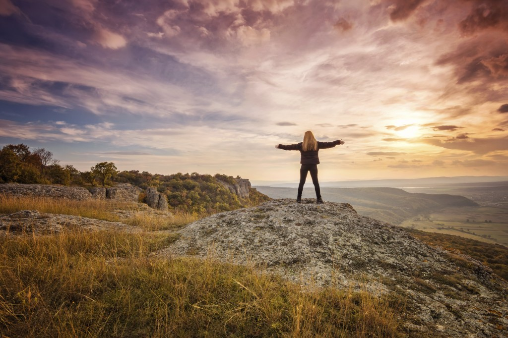 Woman watching Sunset with arms raised