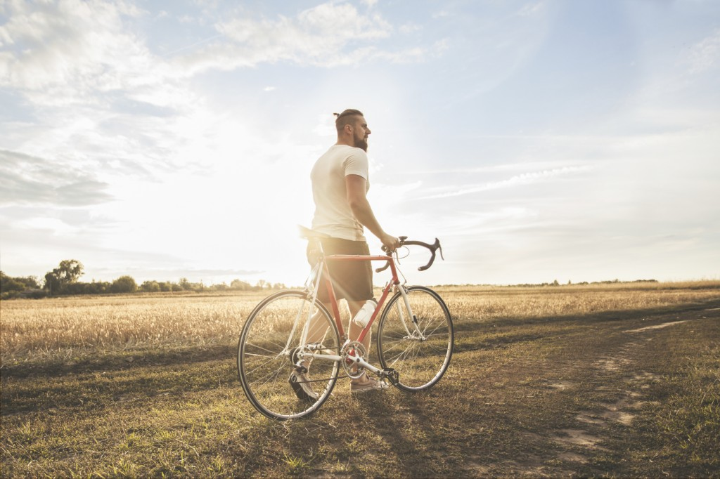 Young hipster man with bicycle