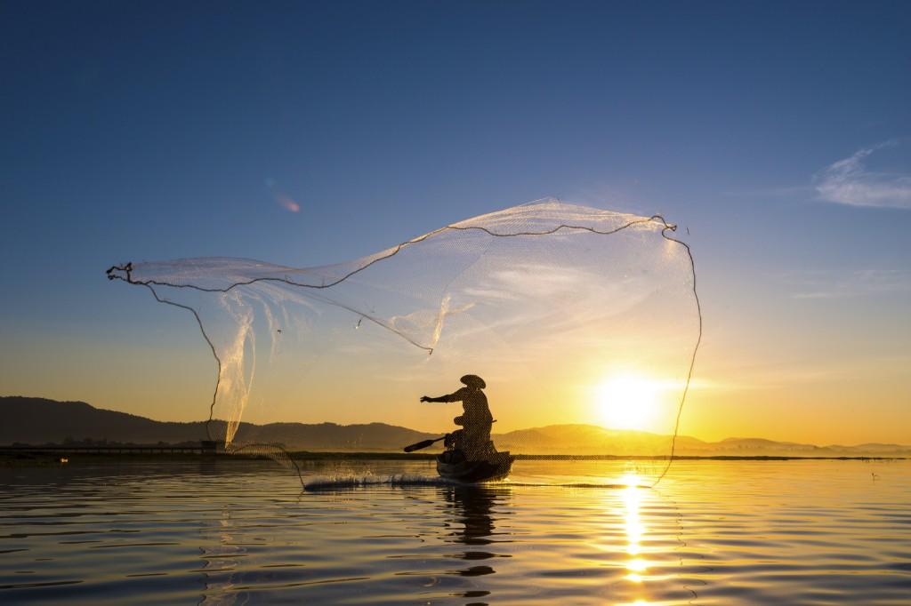 Fisherman in action during fishing in morning