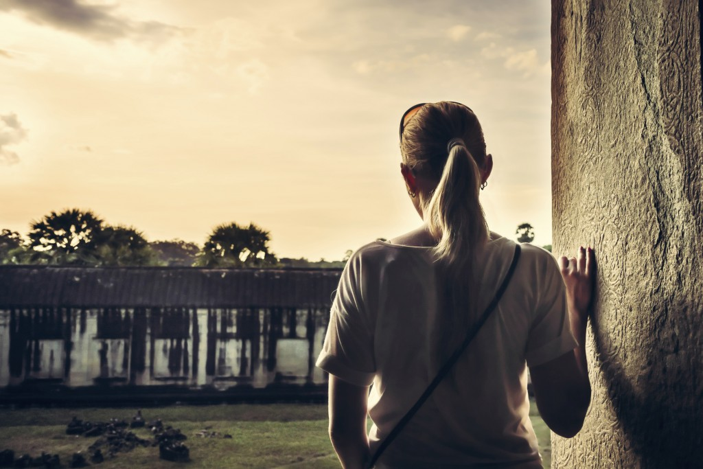 Woman looking at view during sunset through ancient window