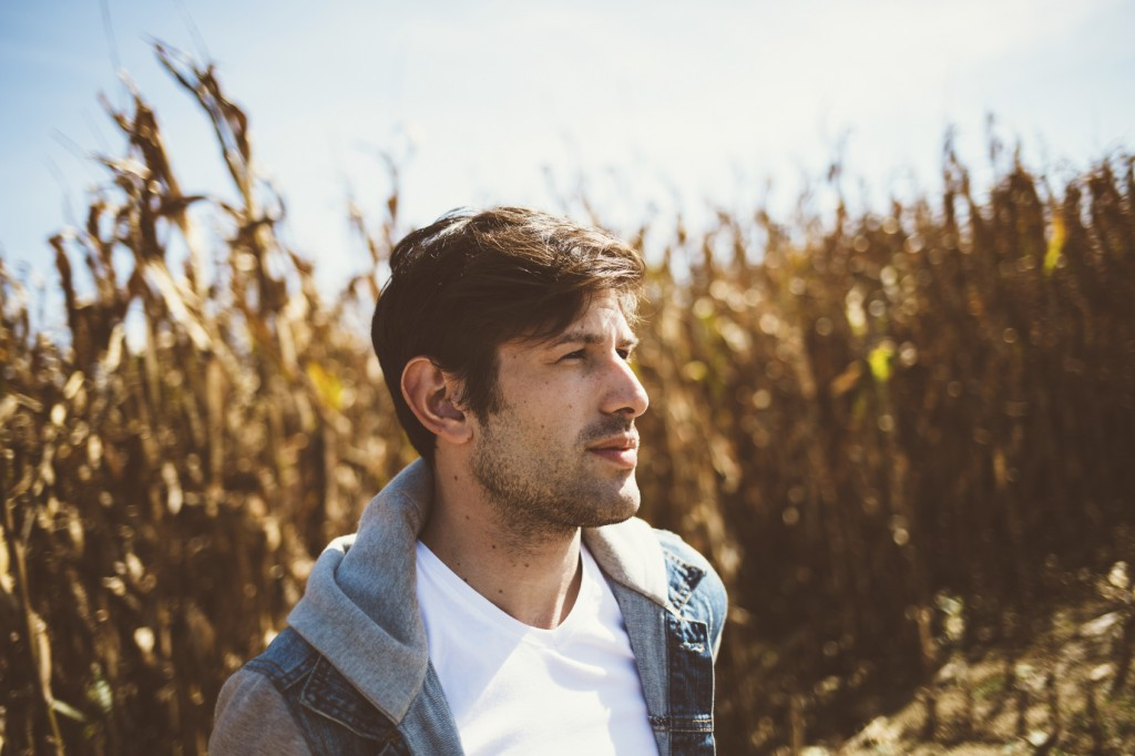 Young bearded man standing in the middle of cornfield