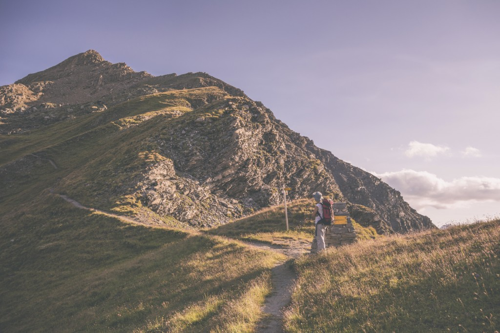 Backpacker hiking on signposted footpath in the Alps