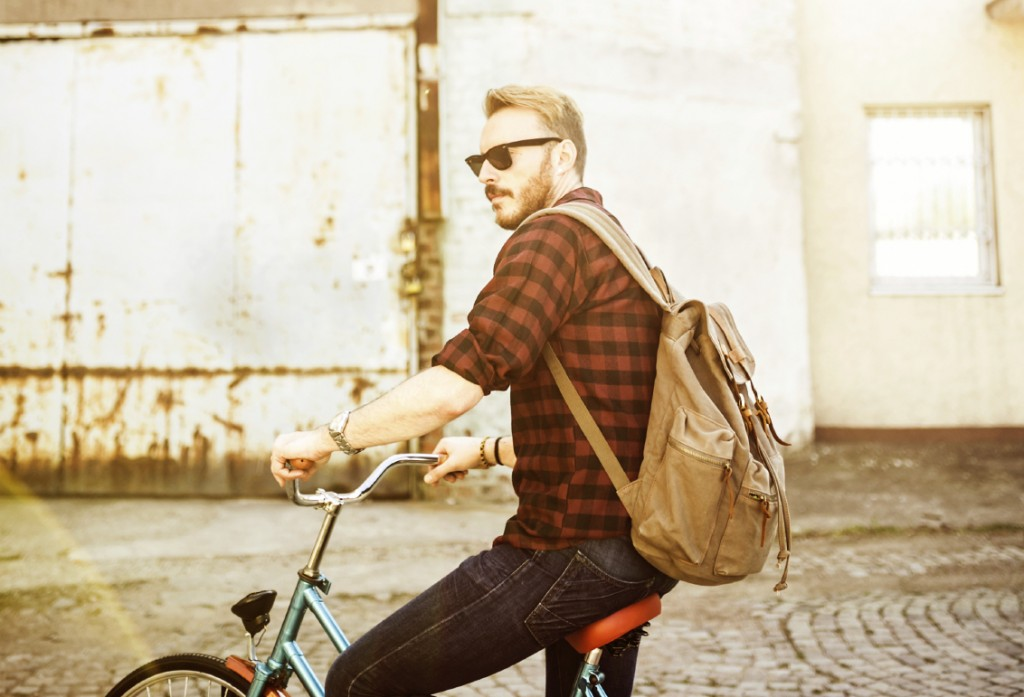 Hipster man on the bike, depth of field, Focus only on jeans and backpack