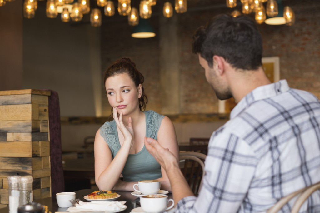 A young couple arguing in a cafe