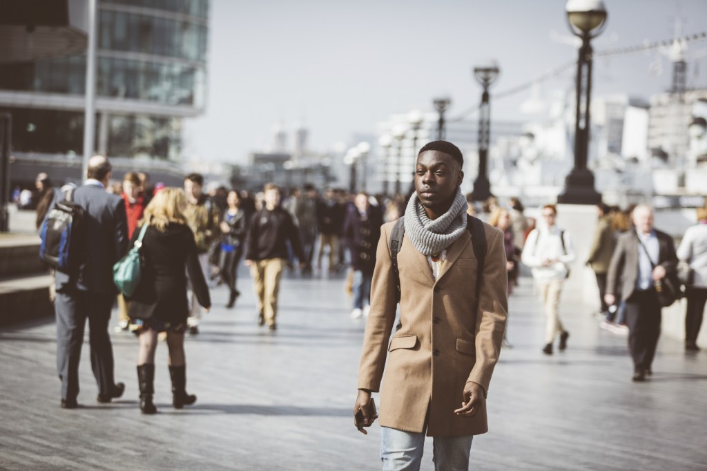 Man walking in London on Thames sidewalk, with blurred people on background.