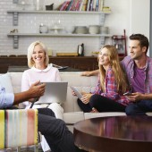 Parents With Adult children Using Digital Devices At Home