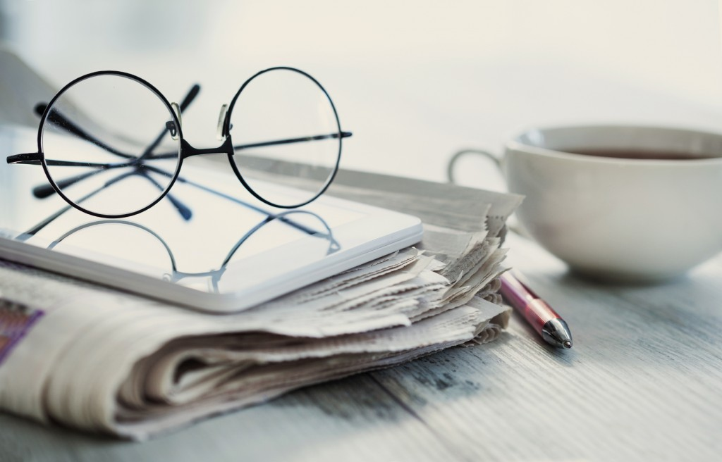 Stack of newspapers, eyeglasses on table -