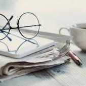 Stack of newspapers, eyeglasses on table -