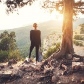 Young woman standing on the mountain near old tree at sunset.