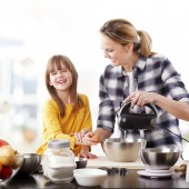 Portrait of adorable little girl and her mother baking together at home.