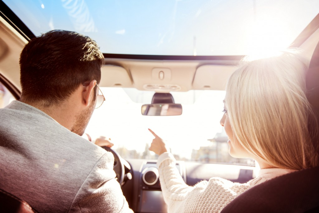 A young woman and a young man are laughing in the car, enjoying in the road trip. The man is driving.