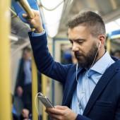Serious businessman travelling to work. Standing inside underground train