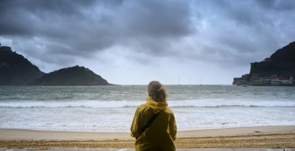 Young girl gazing at the ocean in San Sebastian